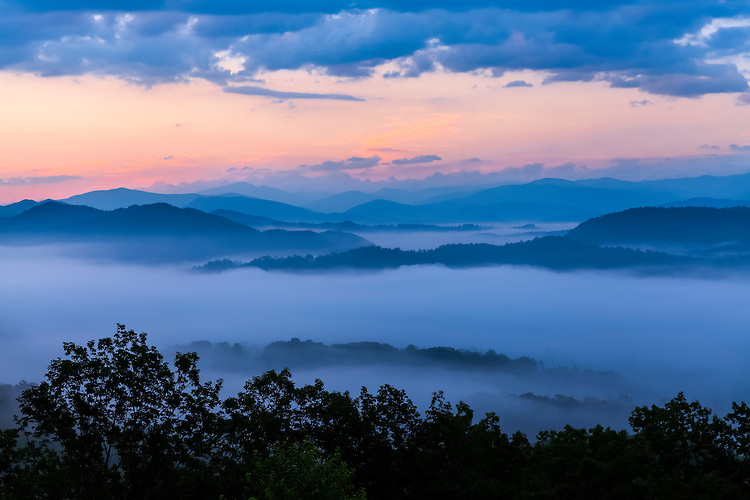 Foggy sunrise color over layered mountains viewed from the Foothills Parkway; Great Smoky Mountains National Park, TN