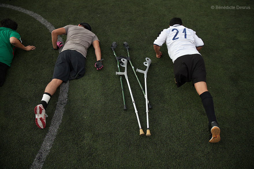 "Players from Guerreros Aztecas, do press-ups as part of their training in Mexico City, Mexico on June 12, 2014. Jose Luis, 32, was washing the windows of his home when he fell 3 metres and lost his right leg. Osman, 31, lost his left leg in a work accident when he was 23. Guerreros Aztecas (""Aztec Warriors"") is Mexico City's first amputee football team. Founded in July 2013 by five volunteers, they now have 23 players, seven of them have made the national team's shortlist to represent Mexico at this year's Amputee Soccer World Cup in Sinaloa this December. The team trains twice a week for weekend games with other teams. No prostheses are used, so field players missing a lower extremity can only play using crutches. Those missing an upper extremity play as goalkeepers. The teams play six per side with unlimited substitutions. Each half lasts 25 minutes. The causes of the amputations range from accidents to medical interventions – none of which have stopped the Guerreros Aztecas from continuing to play. The players' age, backgrounds and professions cover the full sweep of Mexican society, and they are united by the will to keep their heads held high in a country where discrimination against the disabled remains widespread. (Photo by Bénédicte Desrus)"