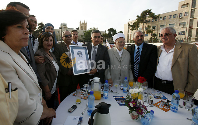 British Jack Brockbank , an international adjudicator from Guinness World Records, presents a certificate to Palestinian Prime Minister Salam Fayad for the longest buffet of natural and organic food setting a new guinness world record, on May 26, 2012 in Arab east jerusalem. The Palestinian banquet, prepared by Jerusalem locals, measured 202 metres. Photo by Mahfouz Abu Turk