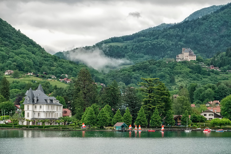 Stately chateaus and lush mountain sides grace the shoreline of Lac d'Annecy in the French Alps.