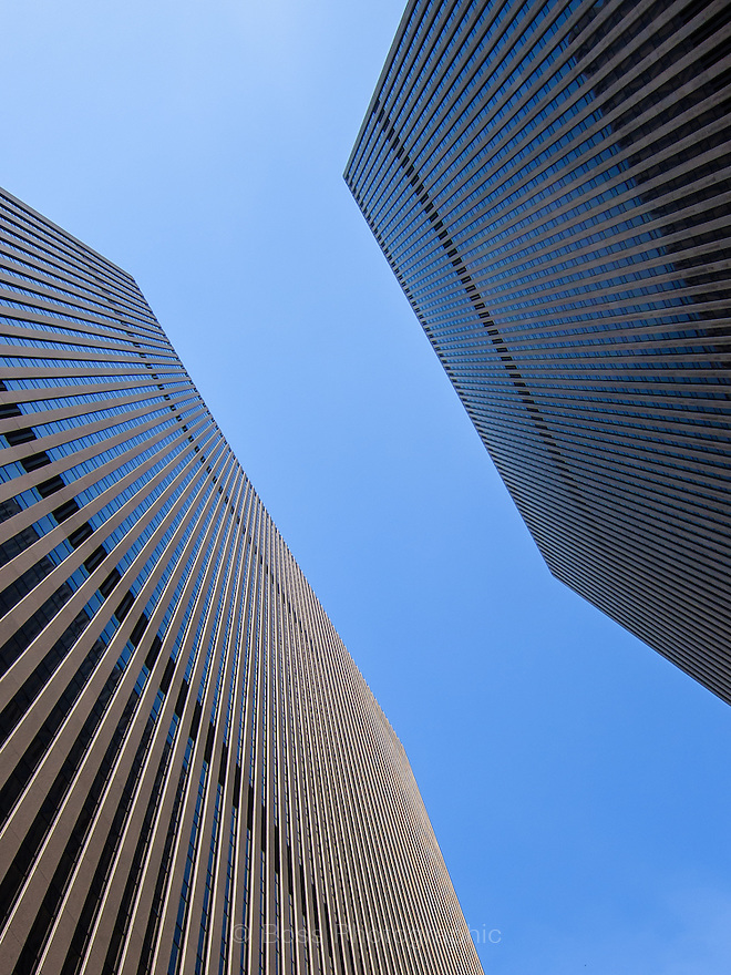Looking up between two tall buildings in Manhattan