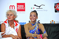 "(L-R) Coach and Daria Dmitrieva of Russia smiles at ""kiss & cry"" at 2010 Pesaro World Cup on August 27, 2010 at Pesaro, Italy.  Photo by Tom Theobald."