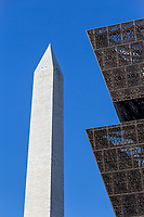The angular metal architecture of the Smithsonian National Museum of African American History and Culture contrasts with the stone structure of the Washington Monument in Washington, DC.