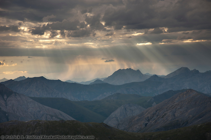 Aerial of dramatic clouds and sunlight over the Brooks range mountains, Alaska.