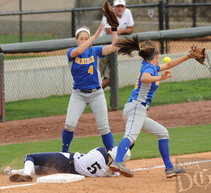 NWA Democrat-Gazette/ANDY SHUPE<br /> Colby Norman (right), third baseman for Sheridan and left fielder Tobi Finley (4) reach to field the throw as courtesy runner Hannah Booker (5) of Greenwood slides in safely at third before scoring Saturday, May 23, 2015, during the fifth inning of the Class 6A state championship game at Bogle Park on the campus of the University of Arkansas in Fayetteville. Visit nwadg.com/photos to see more photographs from the game.