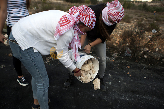 Palestinian girls carry stones during clashes with Israeli security forces in Beit El on the outskirts of the West Bank city of Ramallah, on October 10, 2015. Fifteen Palestinians have been killed by Israeli forces and around 1,000 injured with live and rubber-coated steel bullets in the occupied West Bank and Gaza Strip since Oct. 1. Photo by Shadi Hatem