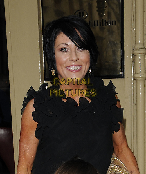 JESSIE WALLACE .Tesco Magazine Mum Of The Year .Awards 2010, held at The Waldorf Hilton Hotel, Aldwych, London, England, UK,.February 28th 2010..Arrivals portrait headshot black smiling wavy neckline trim ruffle neck ruffles top .CAP/CAN.©Can Nguyen/Capital Pictures