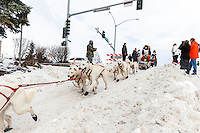 Jim Lanier runs down the Cordova Street hill past spectators and high-five's during the Ceremonial Start of the 2016 Iditarod in Anchorage, Alaska.  March 05, 2016