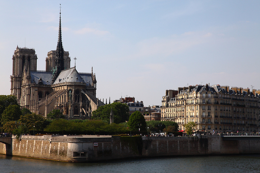A view of the back of the church of Notre Dame in the Île de la Cité in Paris, with the bridge connecting this isle to the Île de Saint Louis. There are a lot of tourists. Digitally Improved Photo.