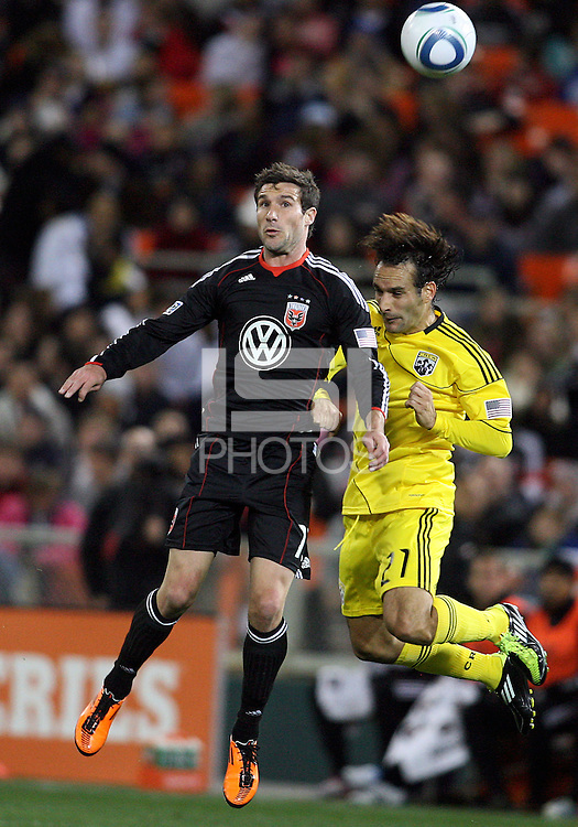 Chris Pontious#13 of D.C. United heads away from Sebastian Miranda#21 of the Columbus Crew during the opening match of the 2011 season at RFK Stadium, in Washington D.C. on March 19 2011.D.C. United won 3-1.