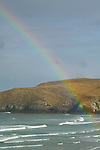 Rainbow over incoming waves, Otago Peninsula, New Zealand
