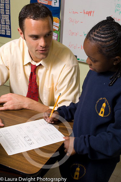 Education Elementary School male teacher working with girl on mathematics in classroom