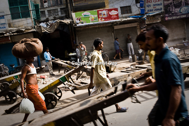Pedestrians and daily paid labourers walk past the busy part of Chandni Chowk, in the old city of Shahjanabad, popularly known as Old Delhi.