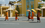 Buddhist monks in the saffron robes walking under umbrellas to shield from the sun