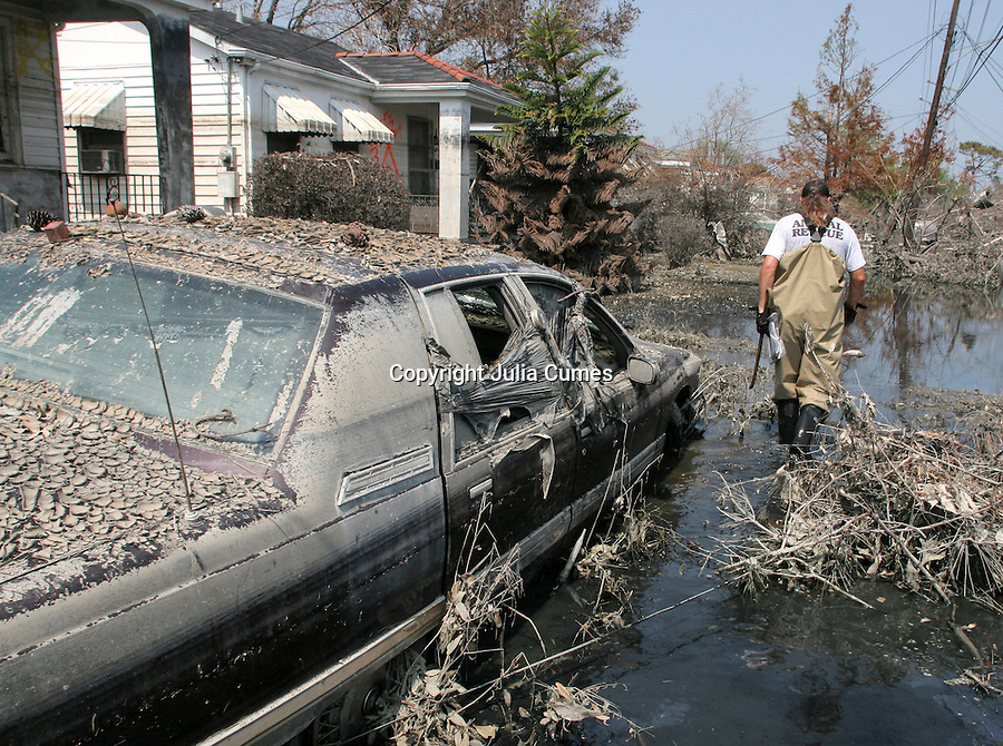 Tim Rickey, of the Humane Society of Missouri, walks through toxic liquid to search for surviving animals in New Orleans three weeks after Hurricane Katrina destroyed the city. Made up of oil, chemicals and sewage, the liquid was so toxic that even mosquitoes were wiped out in New Orleans' flooded areas. Note the high-water mark on the house to the left.