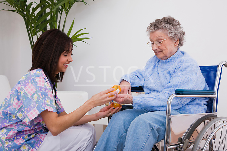 Female nurse giving medication to senior woman in wheelchair