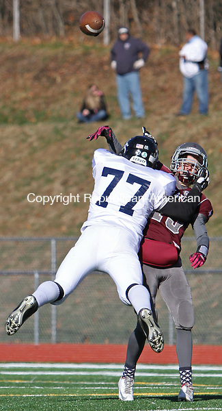 Naugatuck, CT-112813MK08  Ansonia's Tyler Reese (77) puts heavy pressure on Naugatuck's quarterback Jason Bradley (13) during Thanksgiving morning NVL football action at Naugatuck High School.  Ansonia handed Naugatuck their first defeat on the new astroturf 66 to 28. Michael Kabelka / Republican-American