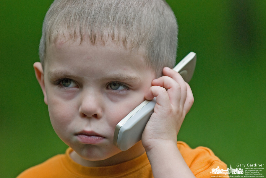 Boy (4-6) talks on a toy cell phone