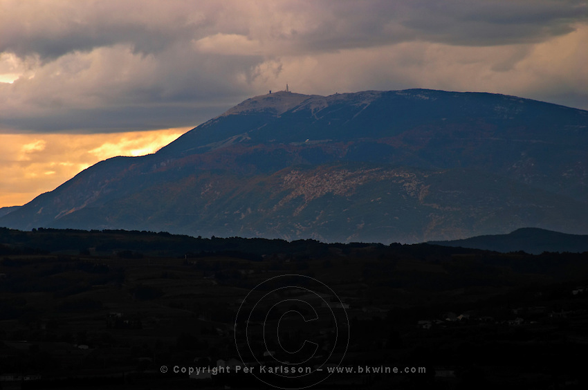 The Mont Ventoux from the north from a distance the top covered in snow. in mist, under storm clouds at sunset.  Vaucluse, France, Europe
