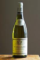 A bottle of Maison Louis Jadot Bourgogne Chardonnay 2002 white burgundy wine standing on a wooden table top. Backlit backlight back light lit. gray grey background sidelit side light, Maison Louis Jadot, Beaune Côte Cote d Or Bourgogne Burgundy Burgundian France French Europe European