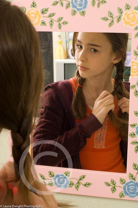 Teenage girl age 13 looking in mirror braiding hair