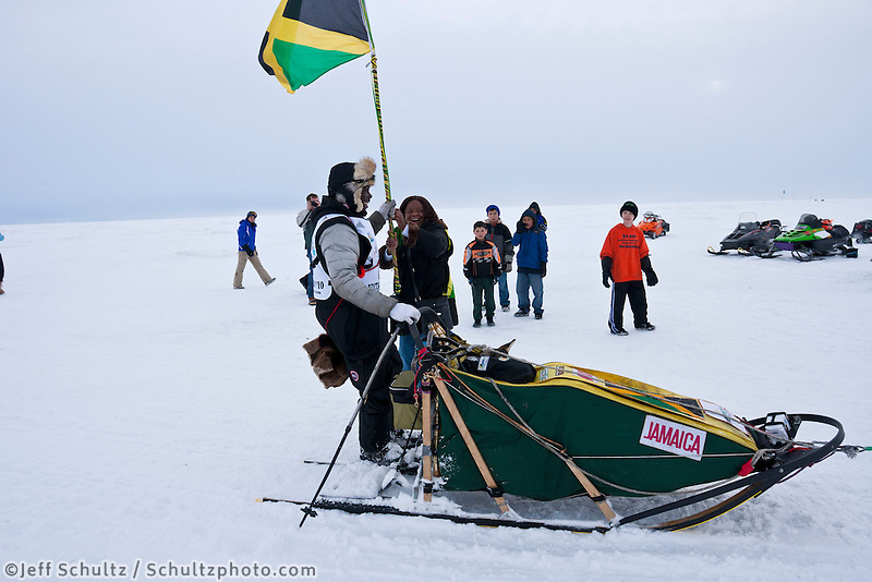 Jamaican, Michelle Heibert, hands rookie musher Newton Marshall a Jamaican flag to hold as he runs the last few hundred yards into the finish line in Nome during the 2010 Iditarod