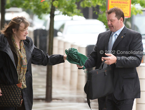 Former New York Yankee pitcher Roger Clemens, right, hands his umbrella to an unidentified person as he arrives at U.S. District Court in Washington, D.C. on Monday, May 14, 2012..Credit: Ron Sachs / CNP.(RESTRICTION: NO New York or New Jersey Newspapers or newspapers within a 75 mile radius of New York City)