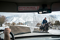 The view through the front window of a car while driving through Kyrgyzstan. A horseback rider passes by.