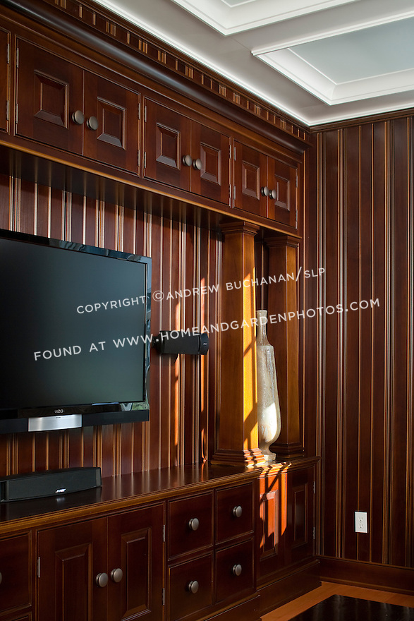 A detail of the built-in entertainment center in the t.v. room / media room of a new contemporary home built in a cleanly-styled, traditional Shaker style.  The dark-stained wooden paneling and built-in floor to ceiling entertainment center were creations of the homeowner, a cabinetmaker with a Master's degree in art who designed the house and crafted all of the cabinetry, built-ins, and most other woodwork himself.