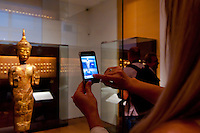 Visitor takes a picture of a golden statue displayed in the Southeast Gold Museum that presents hundreds of golden artifacts from the private collection of founder Istvan Zelnik in Budapest, Hungary on September 15, 2011. ATTILA VOLGYI