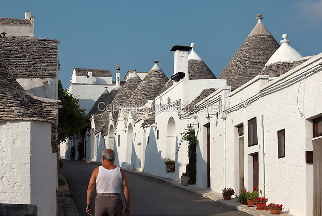 Street of trulli houses made from dry stone (with no mortar), with white-washed limestone walls and conical roofs, in Alberobello, Bari, Puglia, Southern Italy. The area was first settled in the 16th century, and the feudal lord, Count Acquaviva, encouraged his peasants to build trulli to avoid taxes. Alberobello is listed as a UNESCO World Heritage Site. Picture by Manuel Cohen
