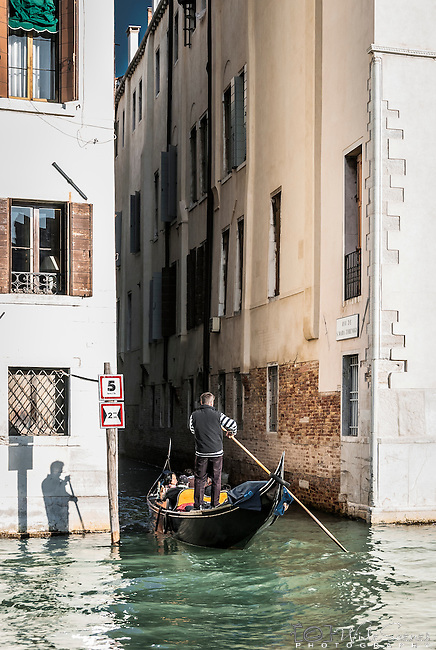A gondolier heading down one of the many canals that meet the Grand Canal in Venice, Italy
