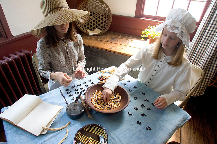WOODBURY, CT- 04 MAY 2008- 050408JT02-<br /> Alicia Belcher, 11, left, of Woodbury, and Kathryn Dolovski, 10, of Middlebury, count out groups of four beans to demonstration math exercises taught during the colonial period at the Glebe House in Woodbury on Sunday during the house's Living History Day event in which costumed docents performed tasks of the Marshall Family, who lived in the Glebe House in the 1770s. Dolovski and Belcher are part of the Marshall Children, an educational after-school program.<br /> Josalee Thrift / Republican-American