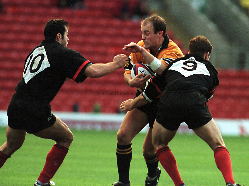Photo. Richard Lane. .Saracens v Wasps. 25/10/98. Alex King prepares to be the filling in a Penaud and Bracken swadwich.