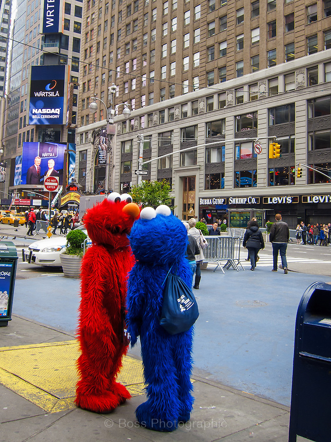 Two people in Elmo and Cookie Monster costumes chatting on a street corner in Times Square