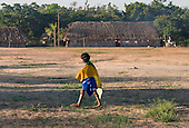 Mato Grosso State, Brazil. Aldeia Metuktire. Child in the village with Brazilian flag draped around the shoulders.