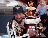 Dale Earnhardt cradles the Winston Cup trophy after clinching his fourth Championship in Atlanta in November 1990.(Photo by Brian Cleary)