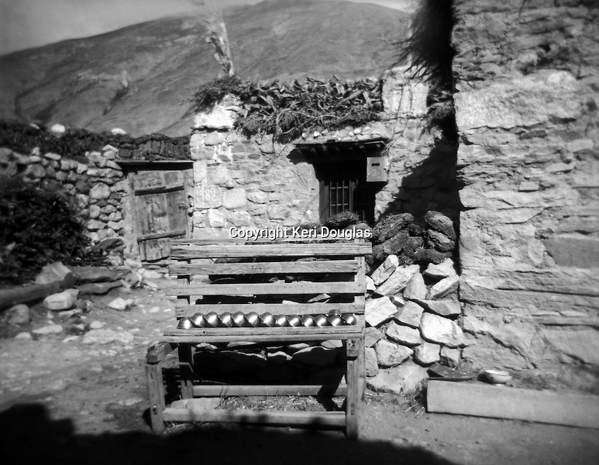 Entrance to Milarepa's cave village with prayer bowls resting on the bench, Tibet
