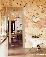 A beaded curtain is caught back across the doorway between the dining room and kitchen, which features a wall of rough adobe