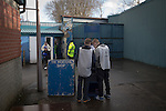 Two young programme sellers waiting for fans inside the stadium before Greenock Morton take on Stranraer in a Scottish League One match at Cappielow Park, Greenock. The match was between the top two teams in Scotland's third tier, with Morton winning by two goals to nil. The attendance was 1,921, above average for Morton's games during the 2014-15 season so far.