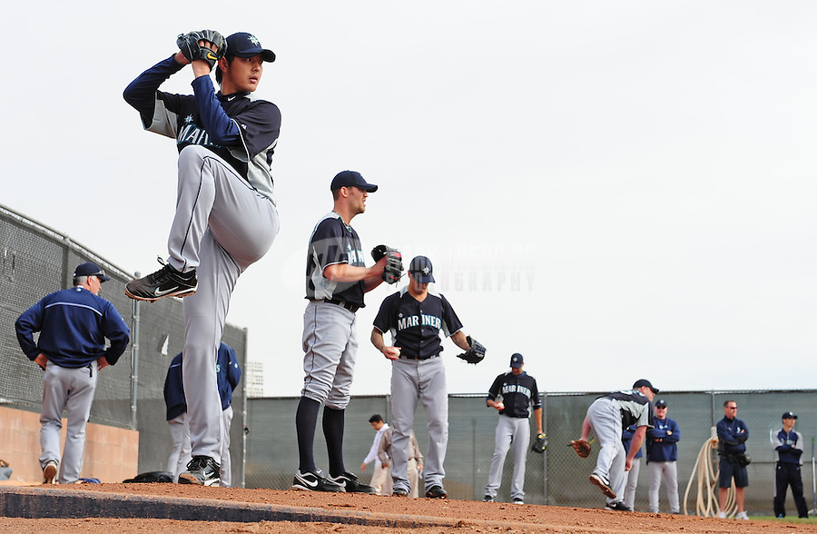 Feb. 15, 2012; Peoria, AZ, USA; Seattle Mariners pitcher Hisashi Iwakuma (left) throws during a pitchers and catchers workout at the Peoria Sports Complex.  Mandatory Credit: Mark J. Rebilas-.