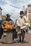 Charles Dickens Festival. Rochester Kent UK. Hurdy Gurdy player with man on simple wooden whistle and drum. 2012.