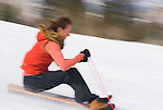 A young woman rides a sled in Jackson, Wyoming (blurred motion).