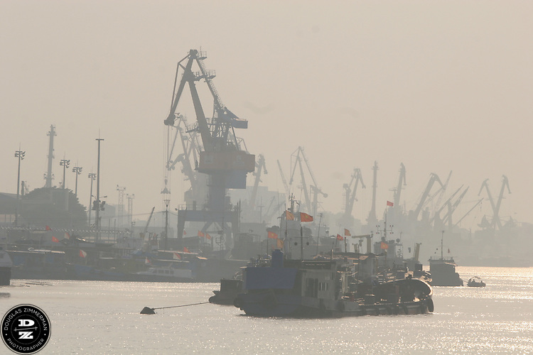 Ships and cranes dominate the shoreline at the port of Haiphong, Vietnam. Haiphong, the third largest city in Vietnam, is an important seaport and industrial center for the country.  Photograph by Douglas ZImmerman