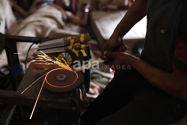 "A Palestinian man grinds a knife at his workshop during the preparation for the upcoming Eid-al-Adha, or ""Feast of Sacrifice"" in Gaza City on October 14, 2013. Millions of Muslims around the world celebrate Eid al-Adha or Feast of the Sacrifice, which marks the end of the annual hajj or pilgrimage to Mecca and celebrates Abraham's readiness to sacrifice his son to God. Photo by Ashraf Amra"