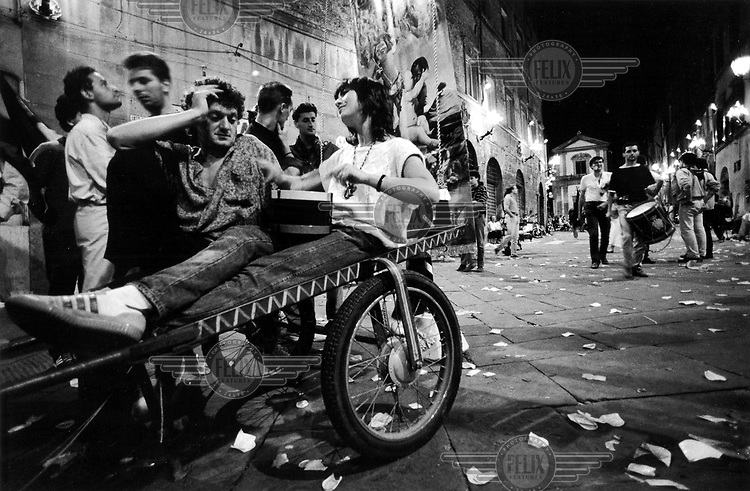 © Francesco Cito / Panos Pictures..Siena, Tuscany, Italy. The Palio. ..The party goes on late into the night after the race...Twice each summer, the Piazza del Campo in the medieval Tuscan town of Siena is transformed into a dirt racetrack for Il Palio, the most passionately contested horse race in the world. The race, which lasts just 90 seconds, has become intrinsic to the town's heritage since it was first run in 1597.