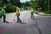 Workers spray paint sections of East Walnut where they replaced ol water lines.
