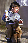 6 May 2001: Child expresses joy of eating a soft ice cream while riding a park toy horse...Mandatory Photo Credit: Ed Wolfstein Photo