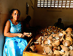 A woman slices coconuts at Coast Coconut Farms, Kenya.   Coast Coconut Farms was started in 2005 by The Pope Foundation as an economic development project with a mission to provide sustainable employment, management and ownership opportunities for the rural people of Kenya