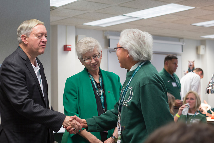 President Duane Nellis and Ruthie Nellis greet Bob Hihida, a professor of osteopathic medicine, Sept. 2, 2017 in the Presidents box at Peden Stadium before the football game against the Hampton Pirates.
